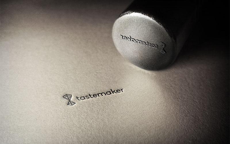 Graphic design mockup of a Tastemaker Supply logo design stamp imprinted on paper.