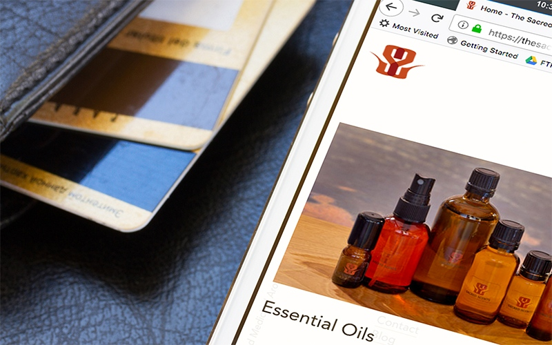 Mockup of thesacredscent.com, a WordPress website, on an iPhone sitting next to a wallet.
