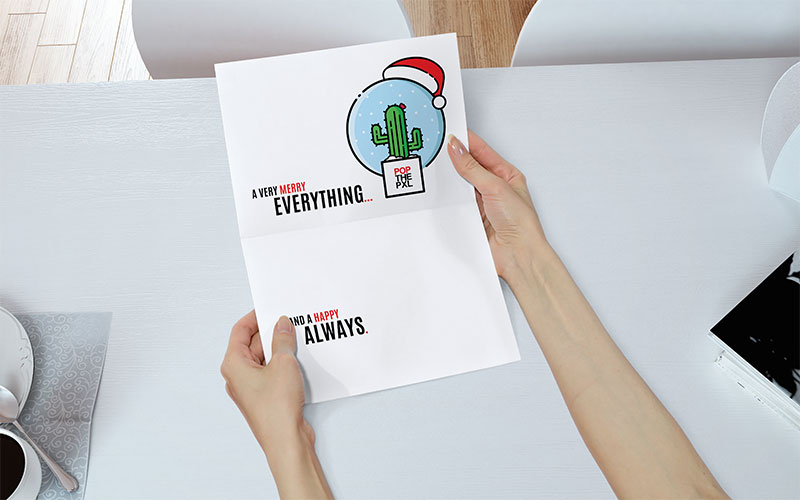Graphic design mockup of a female holding POP THE PIXEL's holiday greeting card.