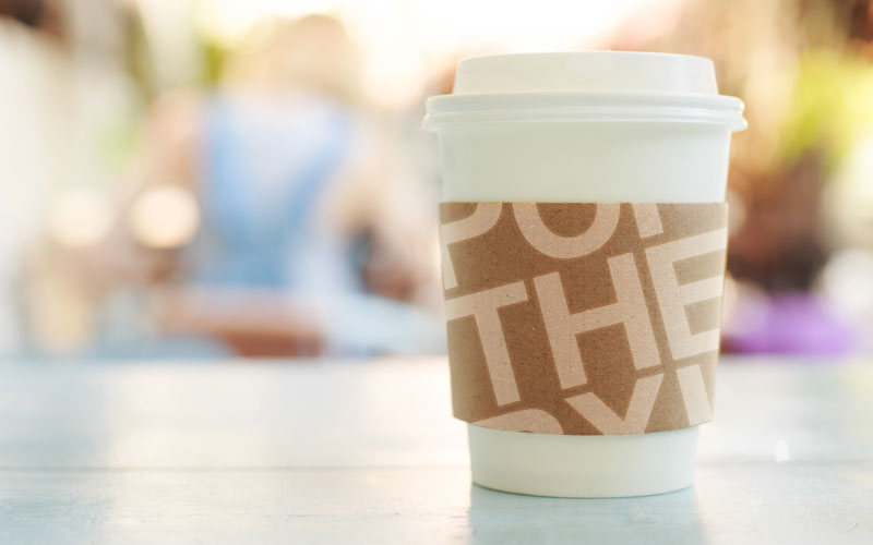 Graphic design mockup of POP THE PIXEL's logo design on a coffee cup sleeve.