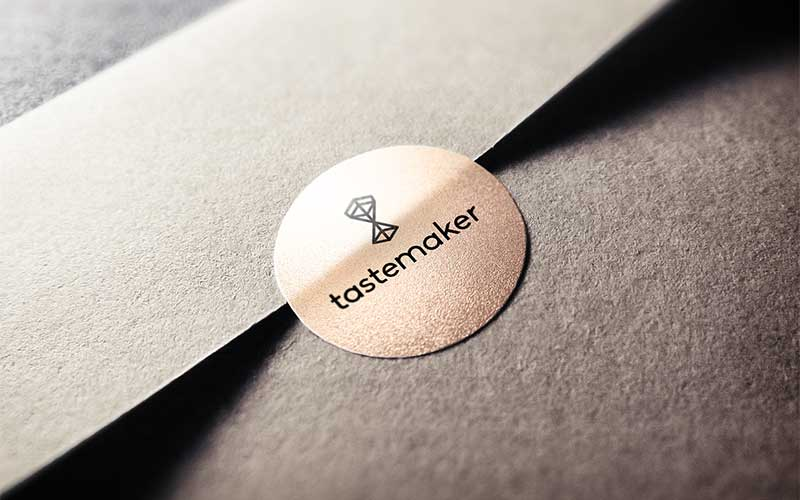 Graphic design mockup of the Tastemaker Supply Co. logo design printed on a sticker.