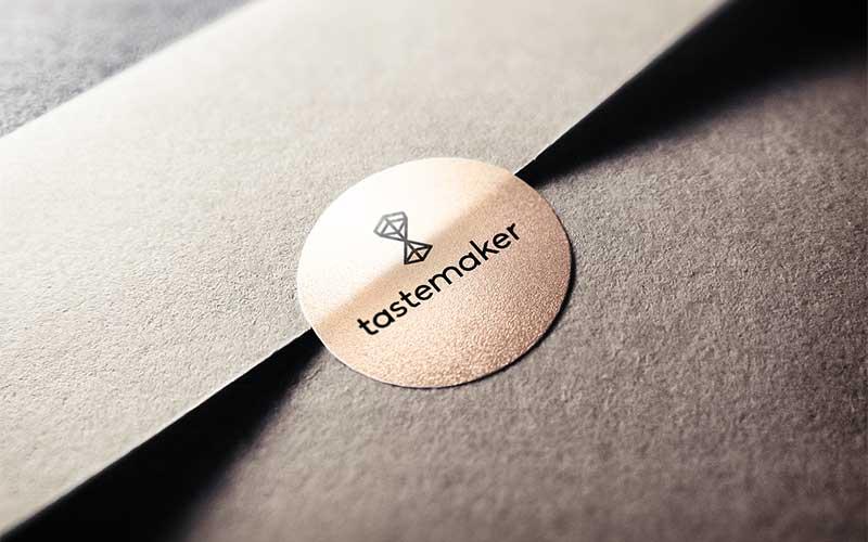 Graphic design mockup of the Tastemaker Supply Co. logo design printed on a sticker.