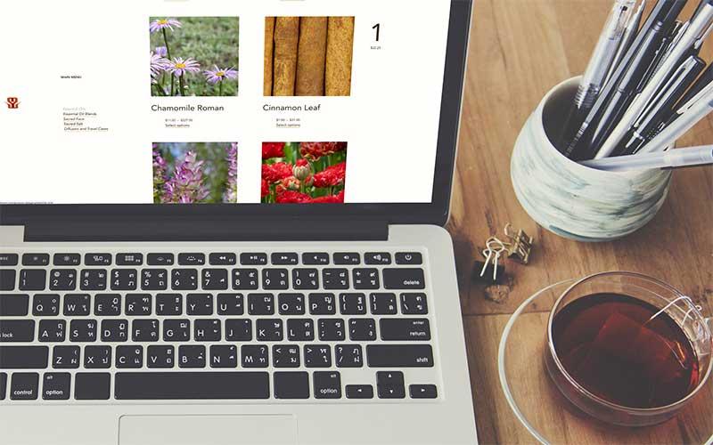 Mockup of thsacredscent.com, a WordPress website, on a laptop.