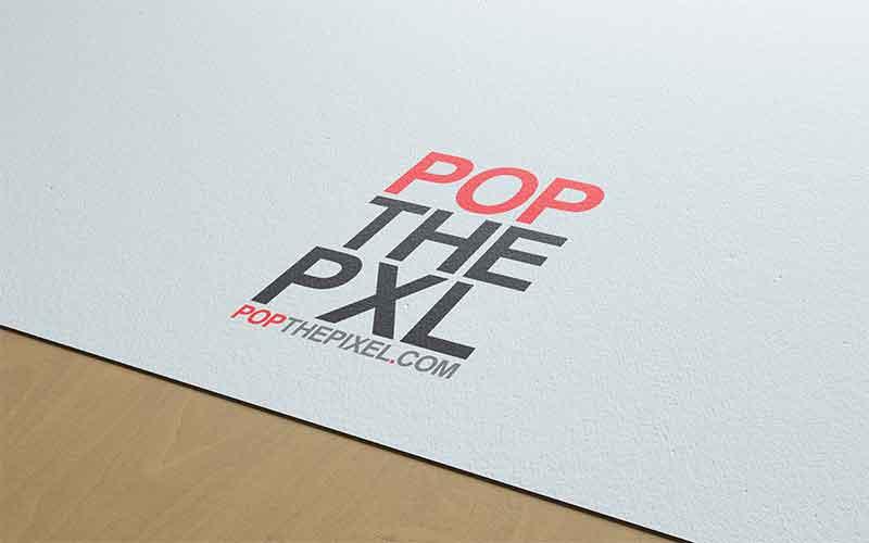 POP THE PIXEL logo design on a sheet of paper.